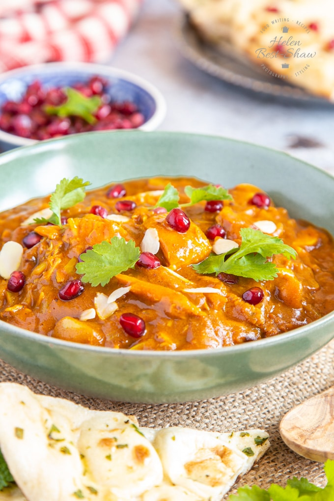 A shallow green bowl full of leftover turkey curry, garnished with almond slices and pomegranate seeds.