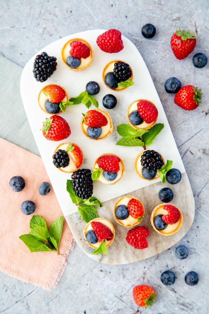 11 mini fruit tarts arranged on a small marble board, garnished with more fruit and mint leaves.
