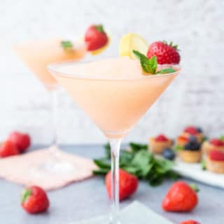 A conical cocktail glass of pale pink strawberry prosecco slushie,