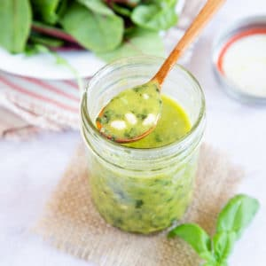 Spooning pesto dressing from a jam jar.