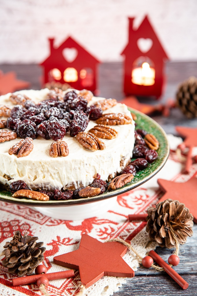 Close up of easy no bake mincemeat cheesecake, topped with pecans and cranberries dusted with icingsugar.