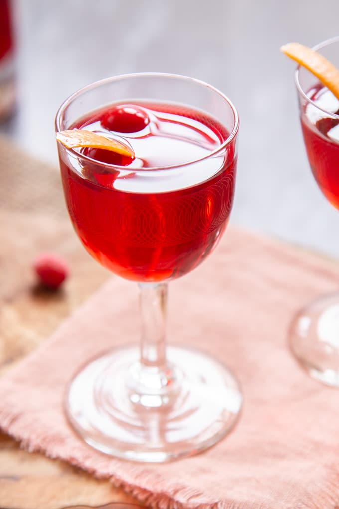 A glass of ruby red cranberry vodka, garnished with cranberries and orange peel.