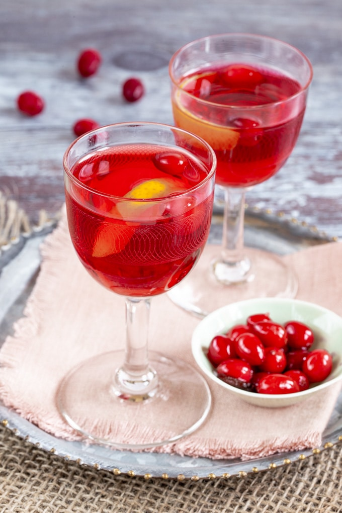 Two liqueur glasses of red cranberry vodka, garnished with cranberries and orange juice.