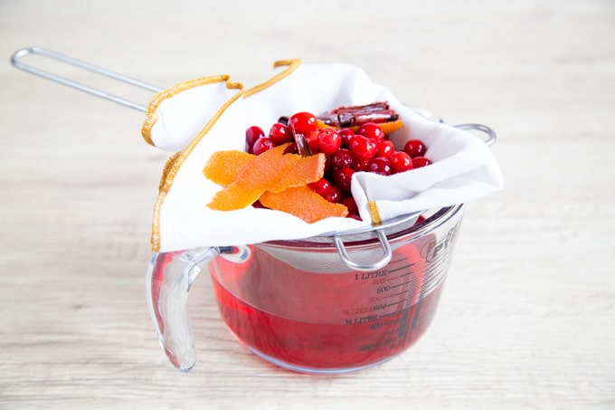 Drained cranberries and orange peel in a cloth lined sieve. A bowl holds the vodka.