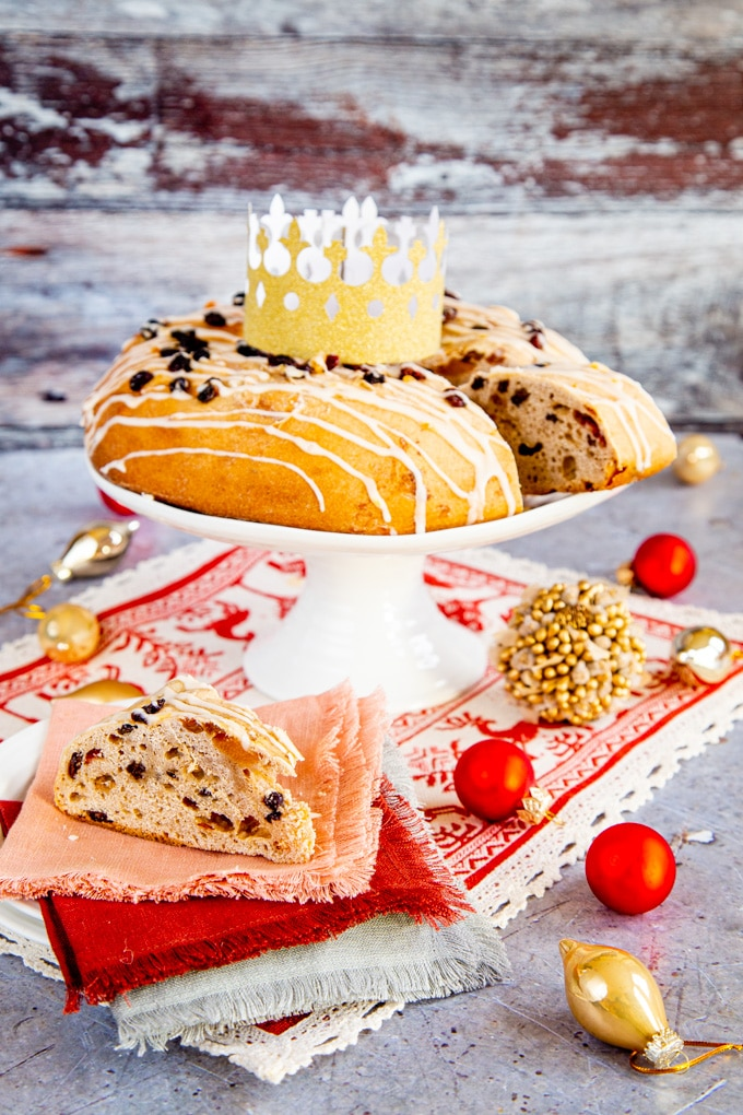 A rosca de reyes fruit cake on a stand, with a slice in the foreground.
