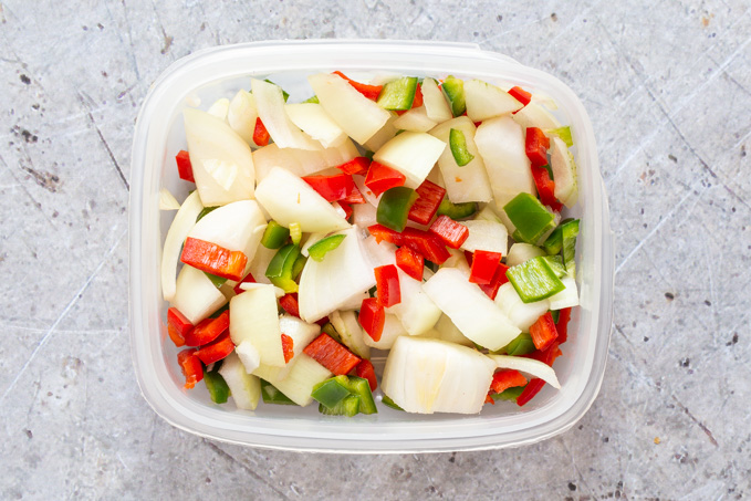 Chopped onion and red and green chillies in a plastic box, ready to be frozen.