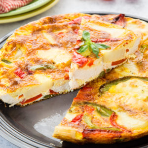 A close up of leftover roast turkey frittata, with a slice cut out and placed on top.