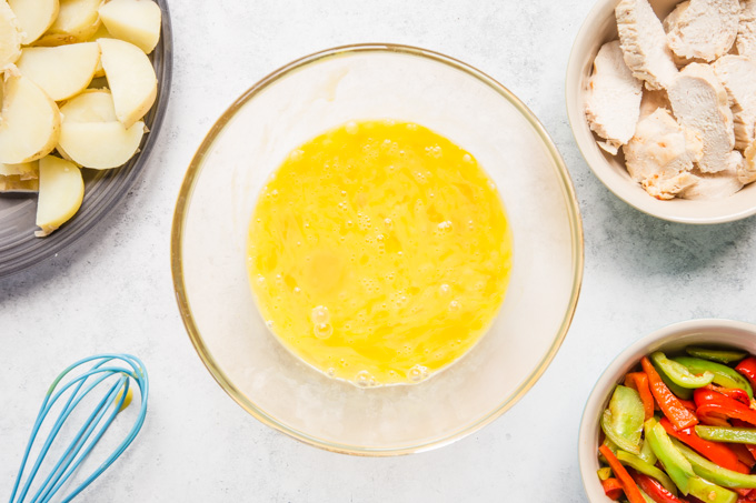 A bowl of beaten eggs surrounded by the ingredients for a turkey frittata