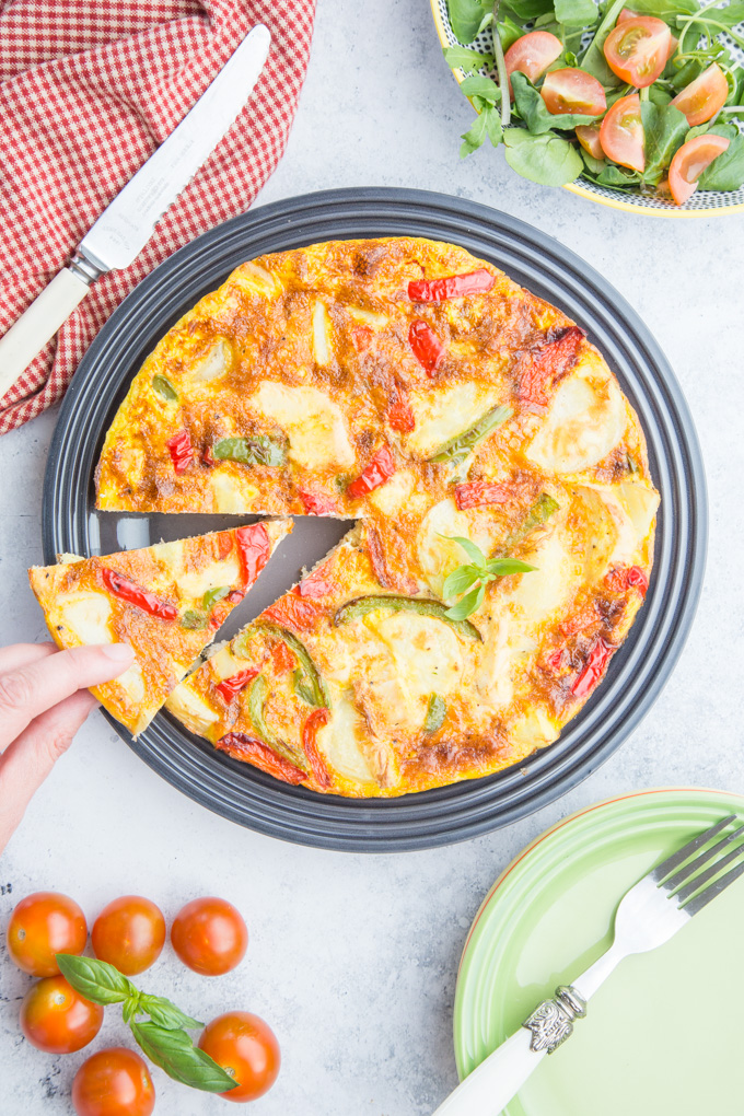 A sliced turkey frittata on a plate viewed from above. A hand holds one of the slices.