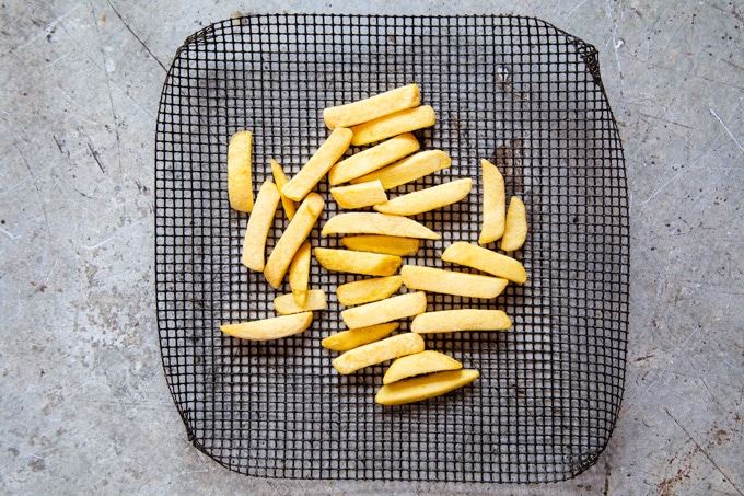 A picture from above of oven chips on a mesh baking tray, ready to be cooked.