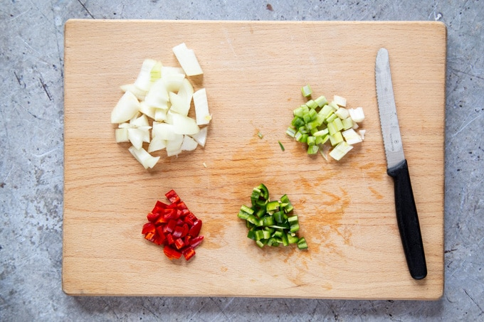 A board of chopped red and green chillies, spring onions (scallions) and onion.