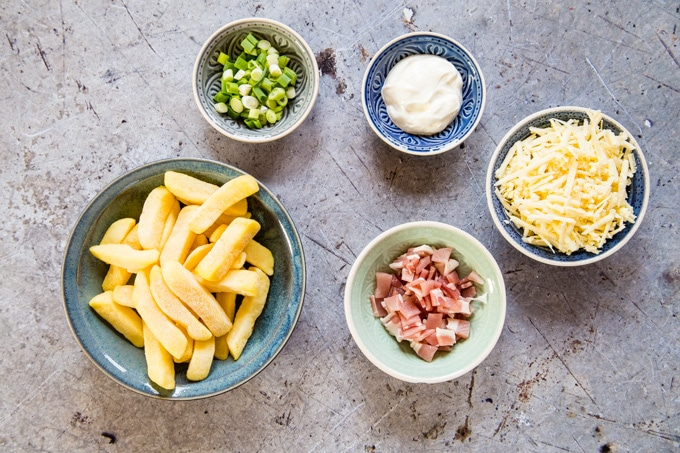 The five ingredients for fully loaded dirty chips - oven chips, bacon, cheese, spring onions and sour cream