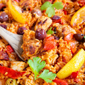A close up of Spanish chicken and rice, with olives, peppers and lemon wedges