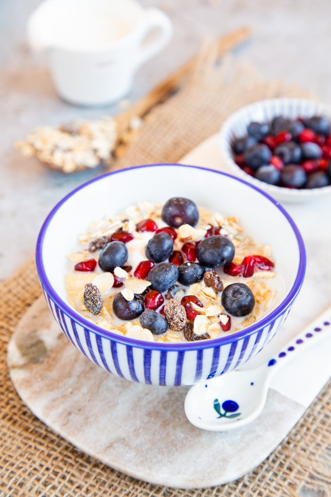 A bowl of economical, delicious home made muesli with milk, pomegrante seeds and blueberries.