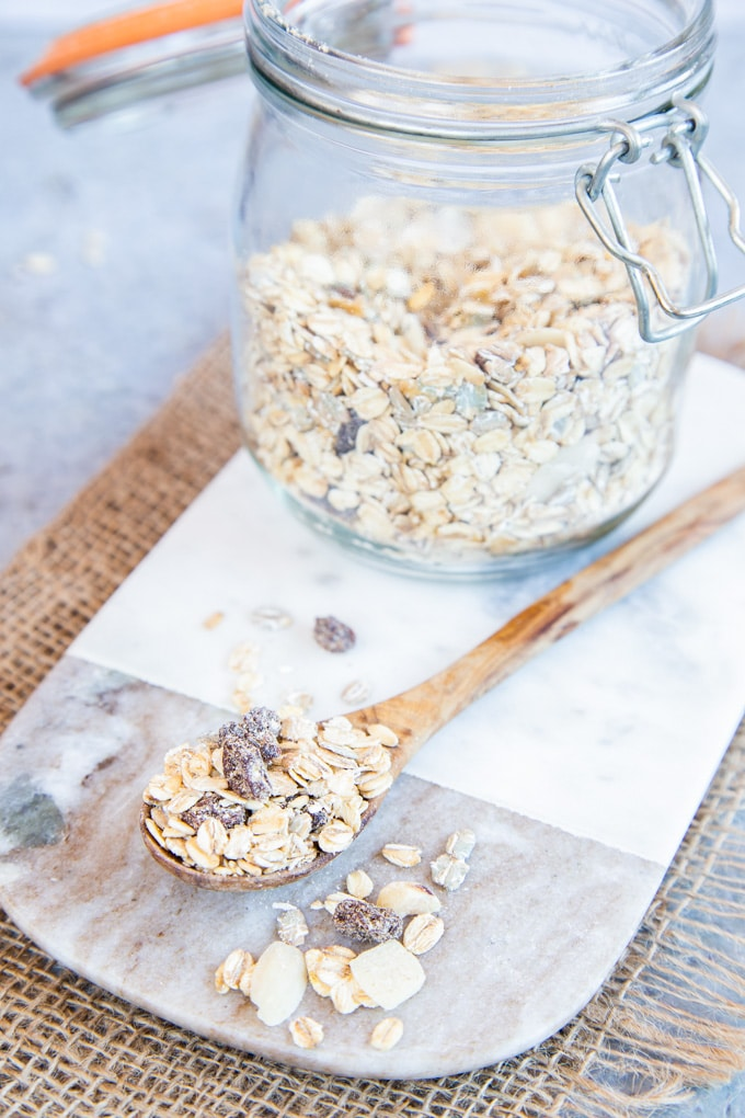 A wooden spoon of our basic muesli recipe on a marble board.