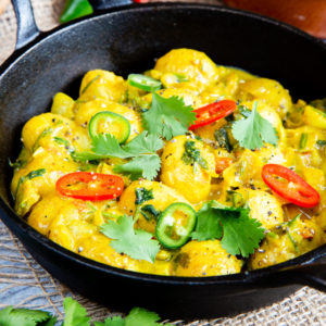 A cast iron dish of golden yellow potato curry garnished with coriander and fresh chillis