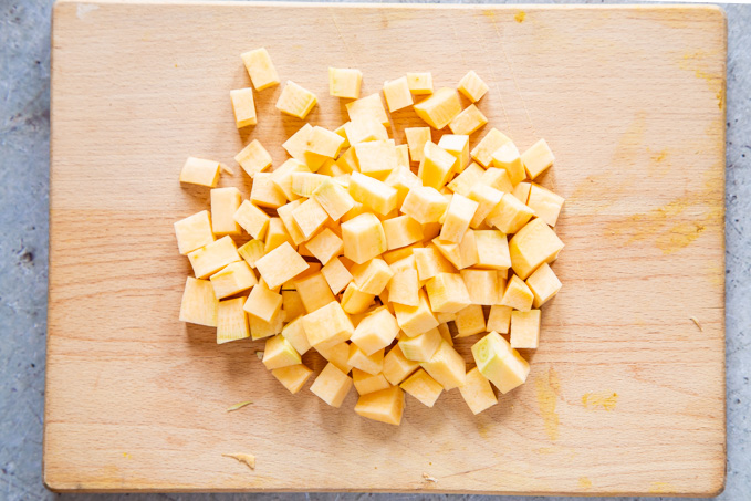A top down view of a wooden chopping board with a piles of cubes of raw swede on it