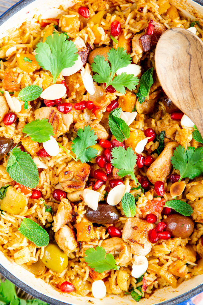 A close up view of a dish of Moroccan chicken with rice garnished with coriander, pomegranate seeds and flaked almonds