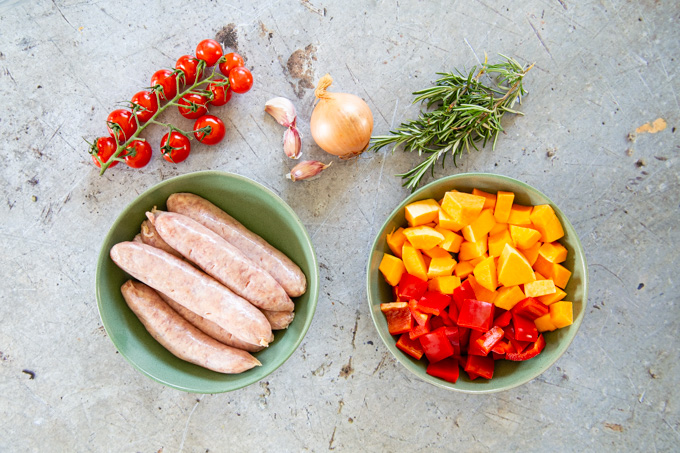The ingredients for the traybake - sausages, peppers, butternut squash, tomatoes, onion, garlic, and rosemary.