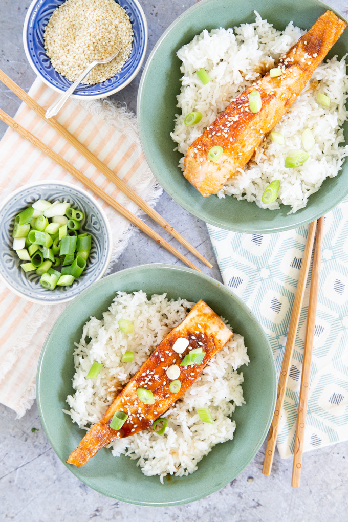 Two green bowls, of easy teriyaki salmon, served on fluffy white rice, from above.