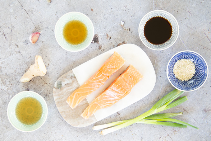 The ingredients for easy teriyaki salmon. The fish fillets are on a marble board in the centre of the shot.