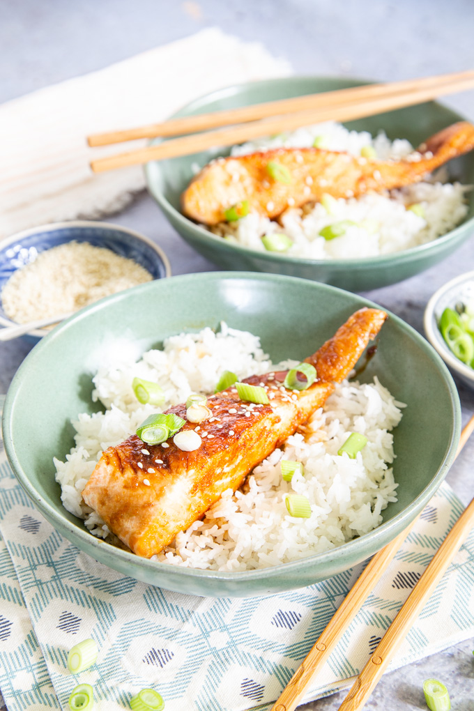 A picture of two fillets of easy teriyaki salmon served in green bowls containing rice.