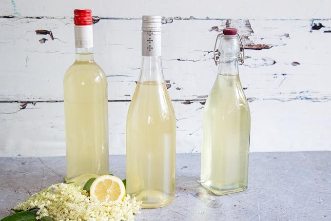 Three bottles of elderflower cordial; a head of elderflower and half a lemon in the foreground.