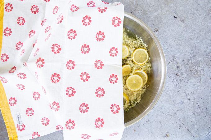 A large bowl of elderflowers steeping in liquid, half covered with a patterned cloth.