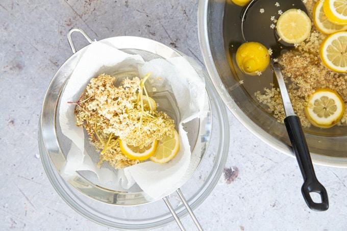 Straining elderflower cordial through a piece of kitchen paper in a sieve.