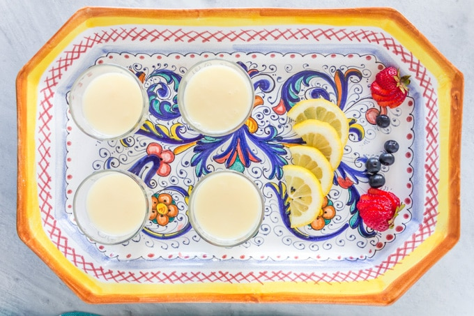 View from above of four individual lemon possets on a colourful plate.