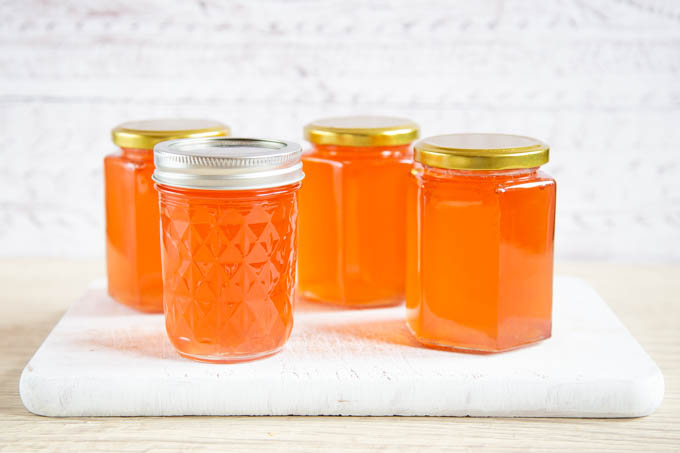 Four pots of pale pink/orange crab apple jelly on a wooden board.