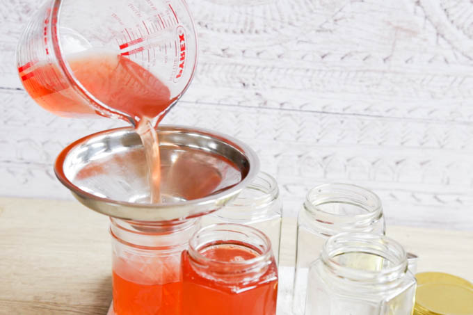 Pouring hot liquid jelly into jam jars, using a jam funnel