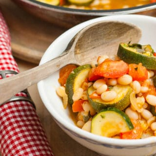 Close up of a white bowl of ratatouille with haricot beans.