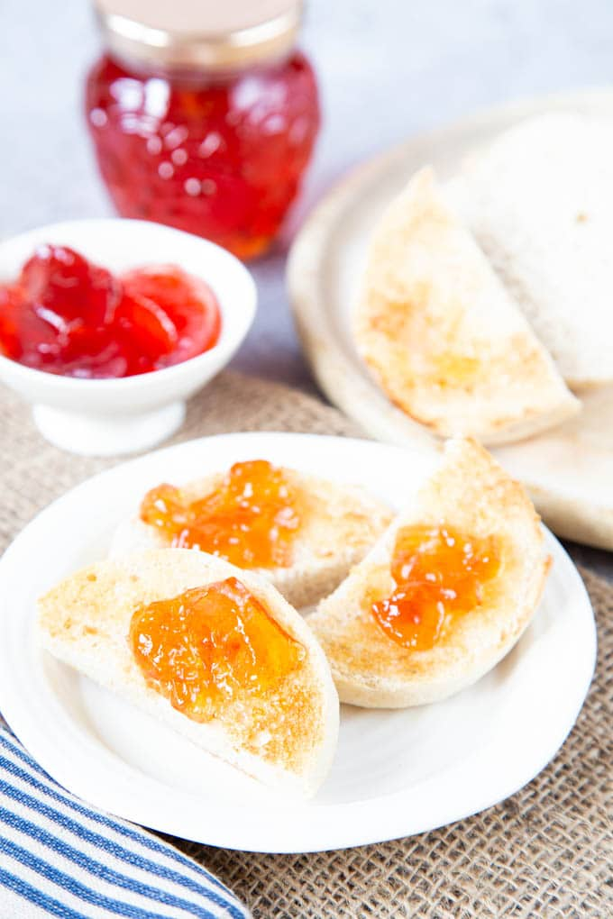 Toasted crumpets spread with butter and pale pink quince jelly on a white plate,
