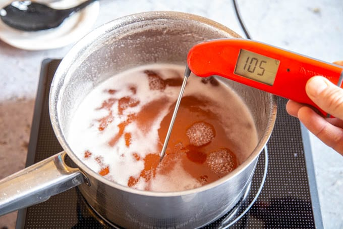 A digital thermometer reading 105C, taking the temperature of a saucepan of jelly.