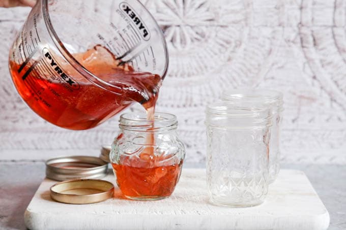 Pouring quince jelly into jam jars from a glass jug.