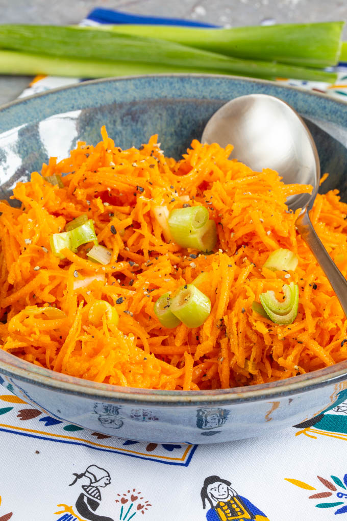 A close up of bright orange grated carrots as a salad.