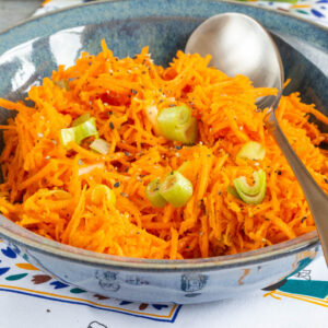 A close up of a blue bowl of easy carrot salad.