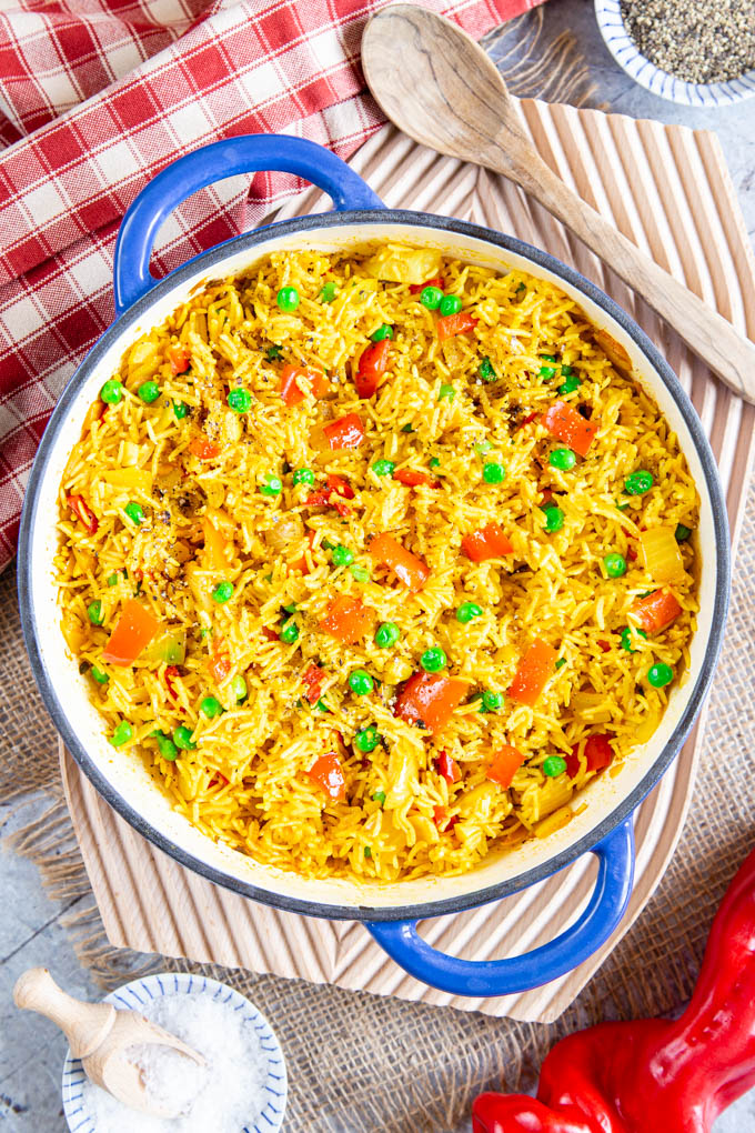 View from above of yellow Portuguese spicy rice, with a sprinkling of red pepper pieces and green peas.