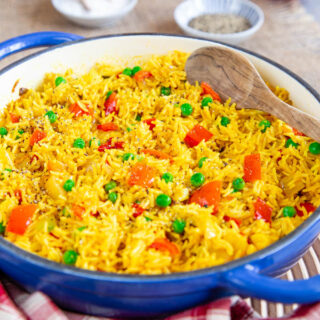 A close up of yellow Nandos Portuguese spicy rice with green peas and pieces of red pepper