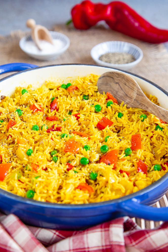 A close up of a shallow blue casserole dish full of yellow spicy rice