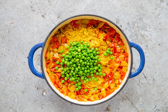 Adding frozen peas on top of yellow spicy rice