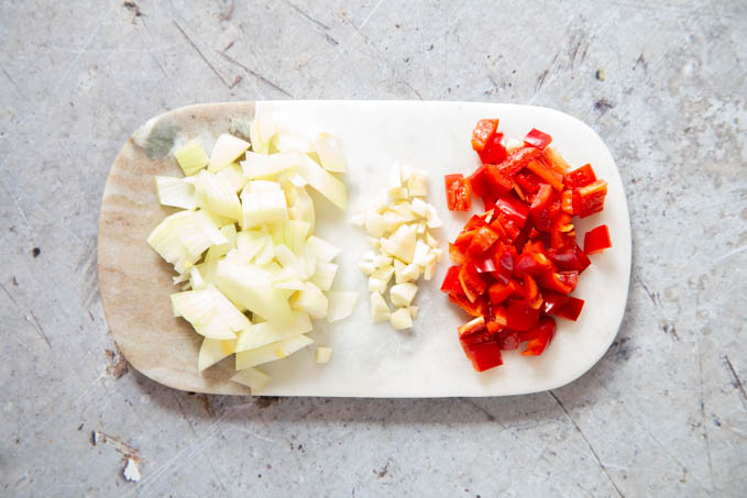 Chopped onion, garlic and red peppers on a marble board.