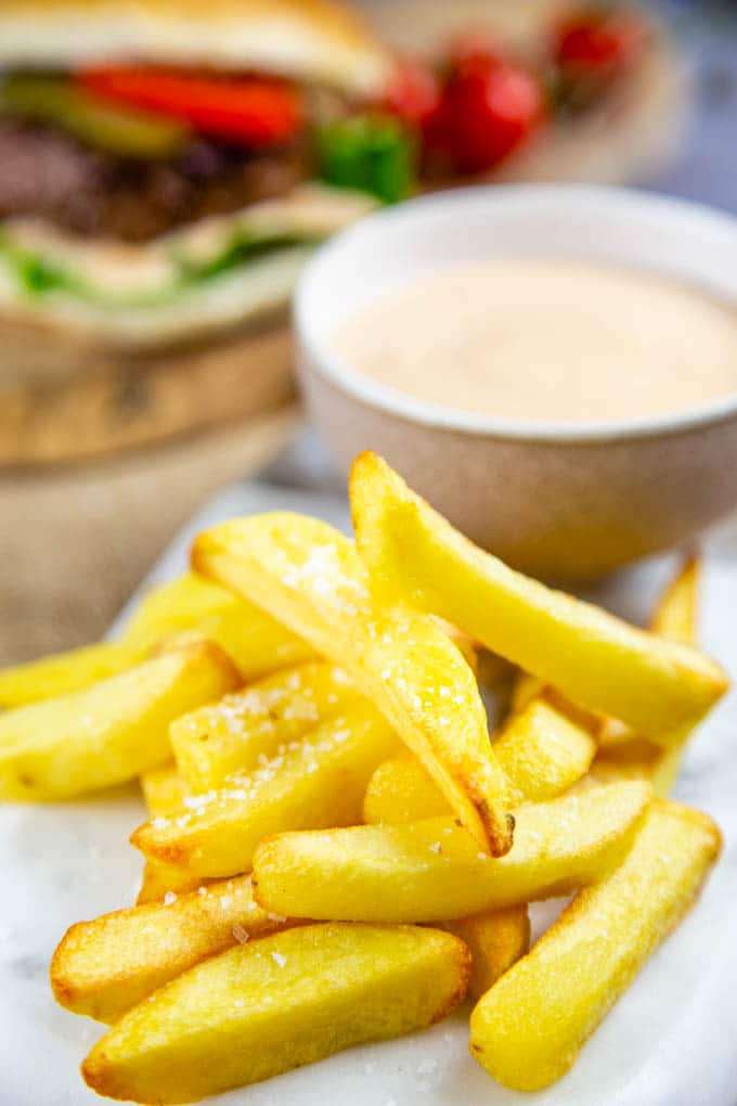 A pile of chips in front of a bowl of burger sauce