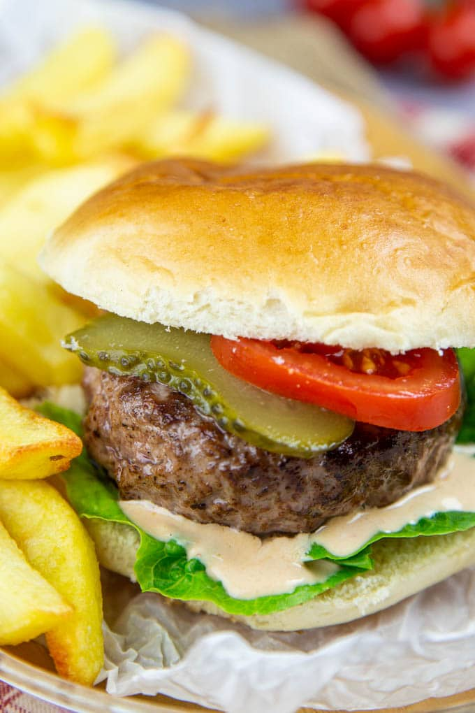 A hamburger in a bun, with lettuce, tomato and pickle, dripping with burger sauce.