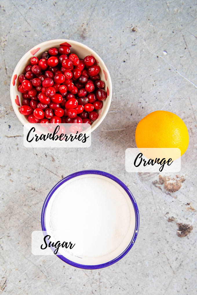 A bowl of cranberries, and one of sugar, and an orange. From above, all three items labeled.