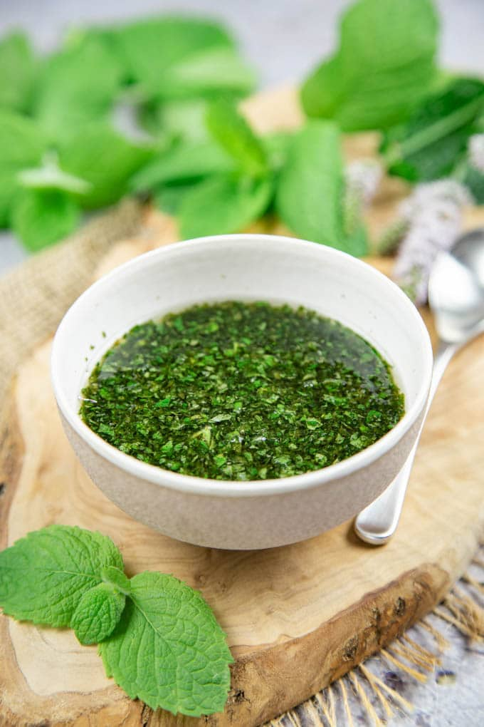 A small bowl of mint sauce, sitting on a wooden board. More mint in the background.