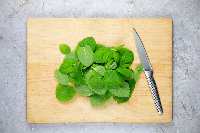 Mint leaves - stalks removed - on a chopping board, ready to cut. A kitchen knife is on the board.