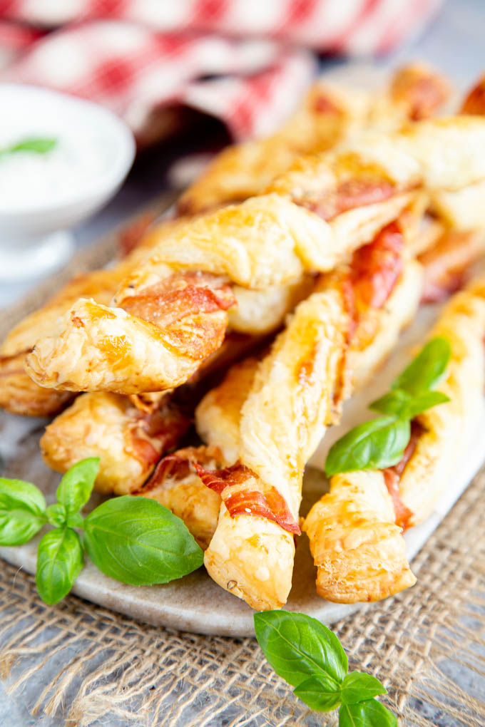 A close up of Prosciutto puff pastry cheese twists on a marble board, garnished with green basil.