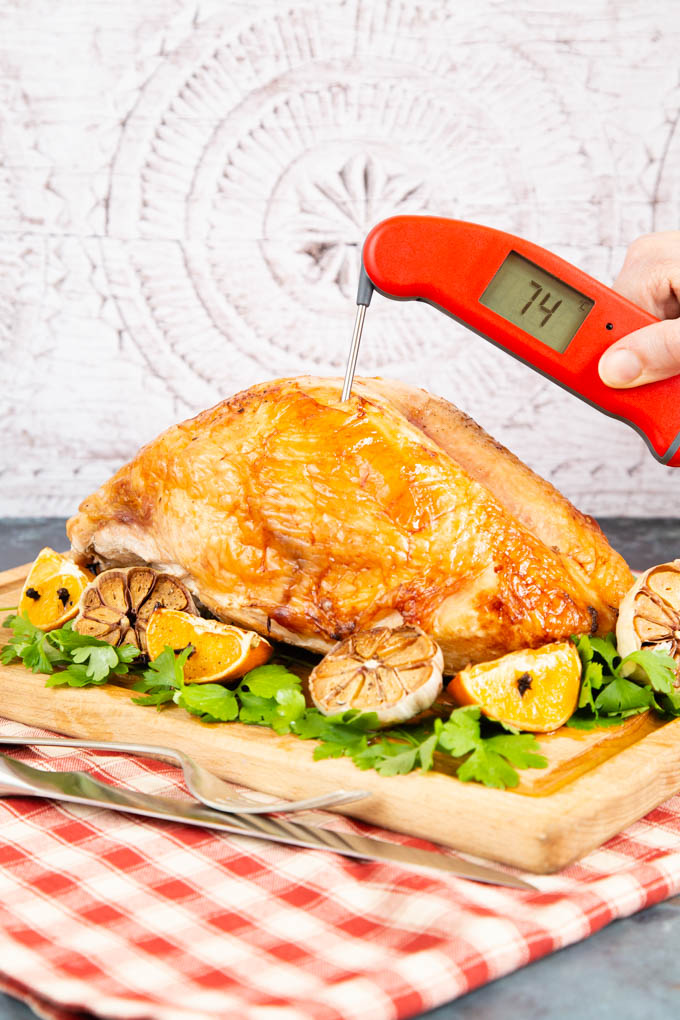 A meat thermometer in turkey crown, showing 74C. The meat is on a wooden board, ready to serve.